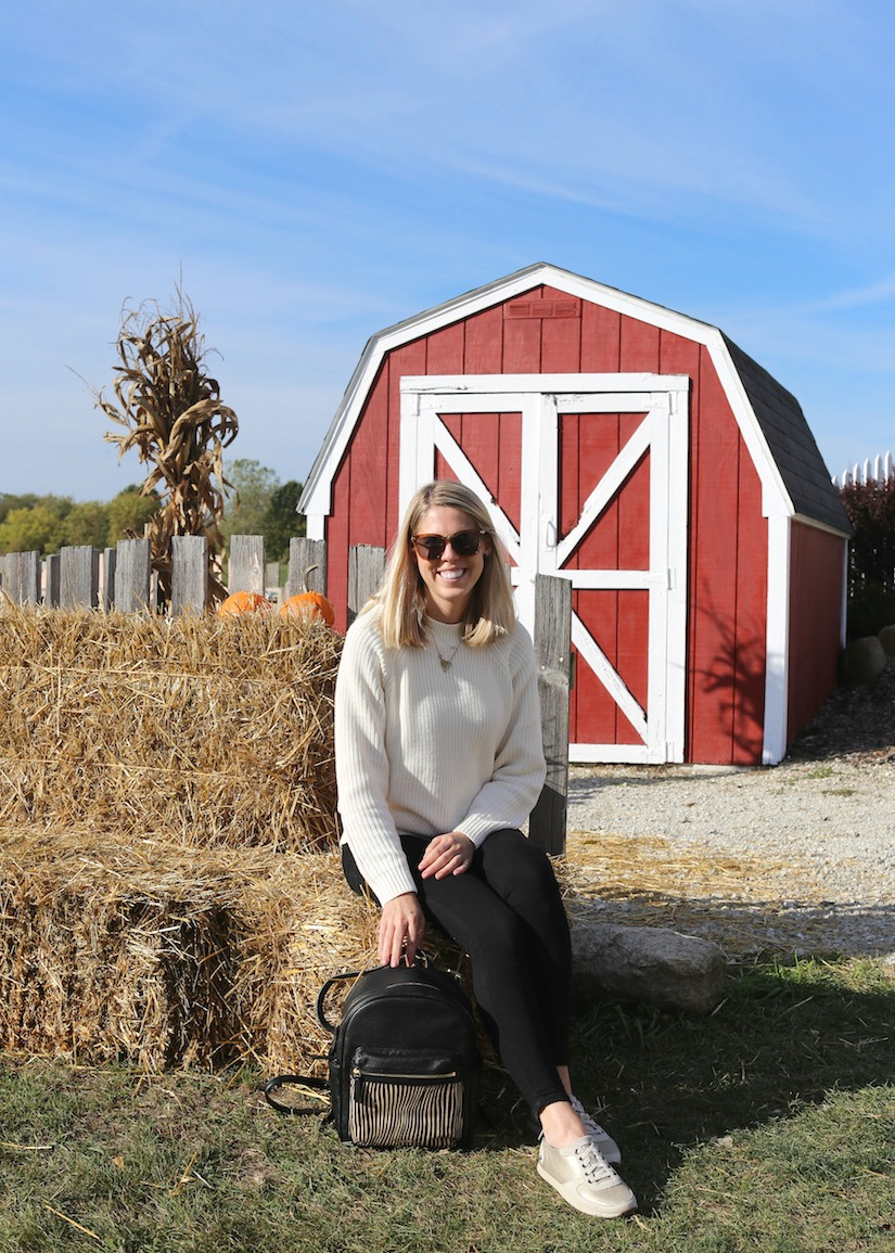 sitting in front of a shed on a hay bale at a farm